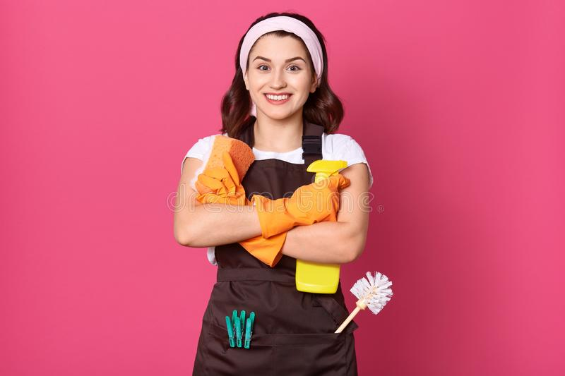 Studio shot of Caucasian young woman wears rubber gloves, apron and hair band, carries detergent, ready to clean house, looks at stock photography