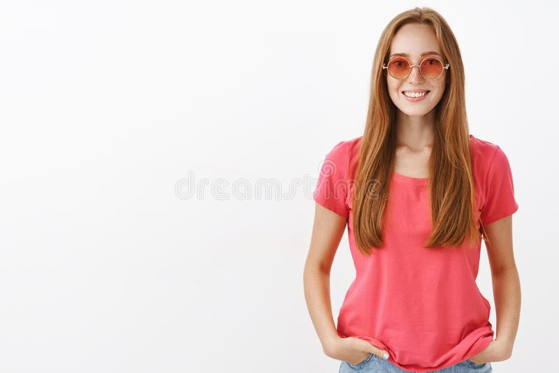 Studio shot of charming friendly-looking hippie girl with ginger hair and freckles holding hands in pockets and smiling stock image