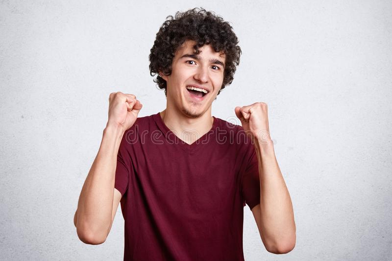 Studio shot of cheerful attractive European male being excited and glad to achieve victory, expresses positivity, clenches fists, royalty free stock image
