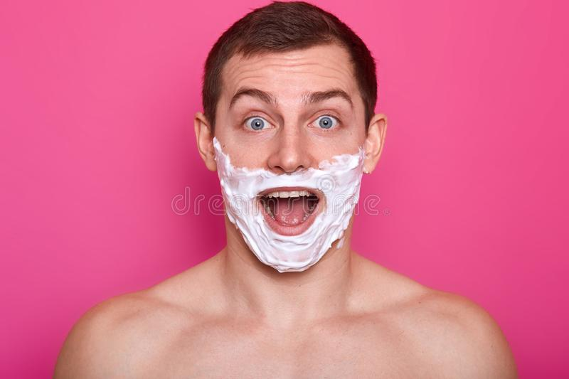 Studio shot of cheerful surprised man with shaving foam on his face looks directly at camera with open mouth, has astonished royalty free stock photography