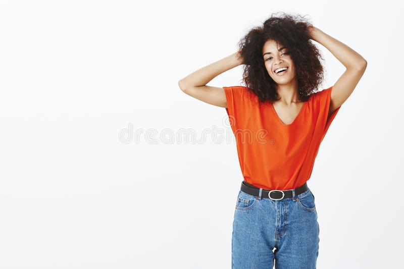 Studio shot of chill outgoing african american woman with afro hairstyle holding hands on back of head and gazing at. Camera with charming smile, being in great royalty free stock image