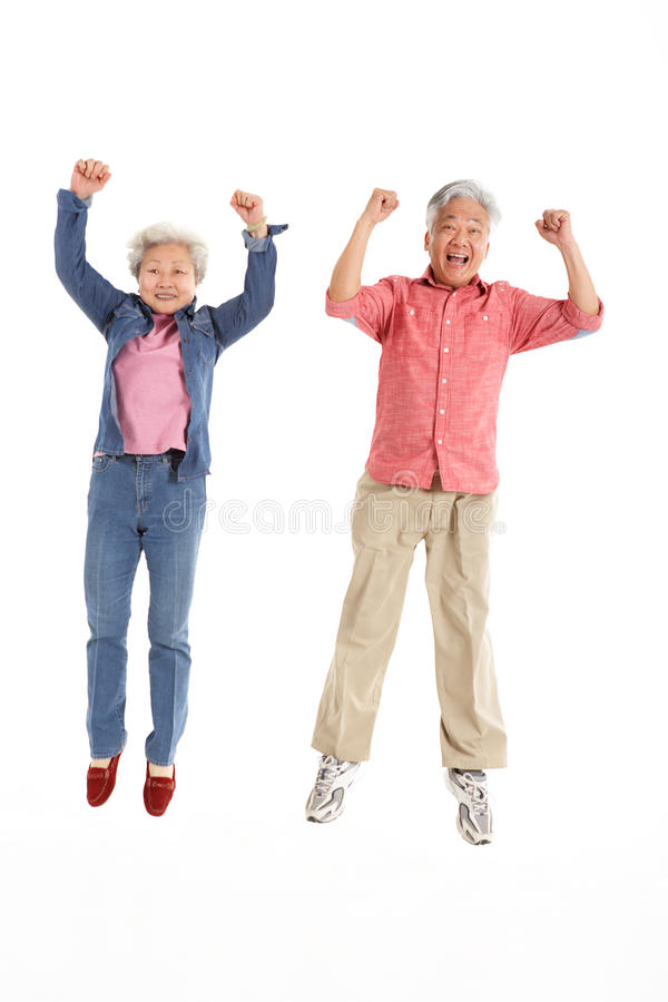 Studio Shot Of Chinese Senior Couple Jumping royalty free stock photography