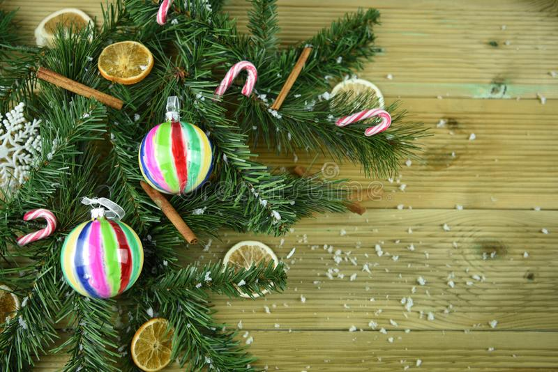 Christmas photography image with green tree branch leaves cinnamon orange slices and colorful bauble decorations and snow. Studio shot with Christmas tree stock photo