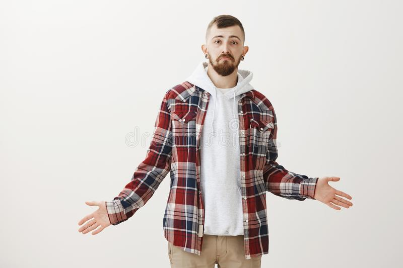 Studio shot of clueless indifferent funny bearded guy with stylish haircut in trendy outfit, spreading hands cluelessly. And making sturgeon face, being unware royalty free stock photography