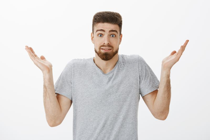 Studio shot of clueless unaware handsome bearded man shrugging with raised hands and eyebrows making silly clueless. Expression cannot answer question being royalty free stock photo