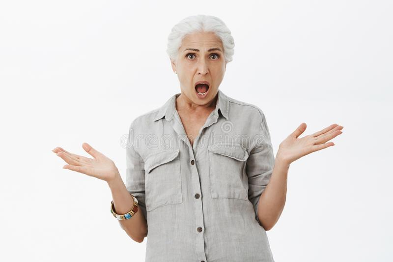 Studio shot of confused and displeased shocked senior mother with white hair shrugging raising palms aside questioned royalty free stock image
