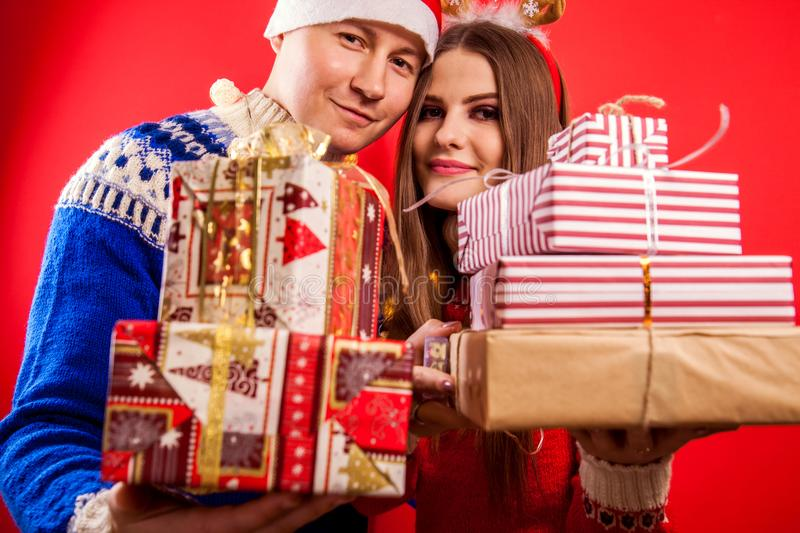 Studio shot of a couple in Icelandic sweaters holding gift boxes. Christmas or New Year celebration concept. stock photo