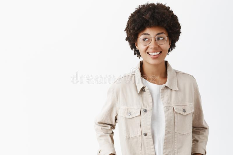 Studio shot of creative confident and carefree dark-skinned female freelancer in beige shirt and glasses holding hands royalty free stock image