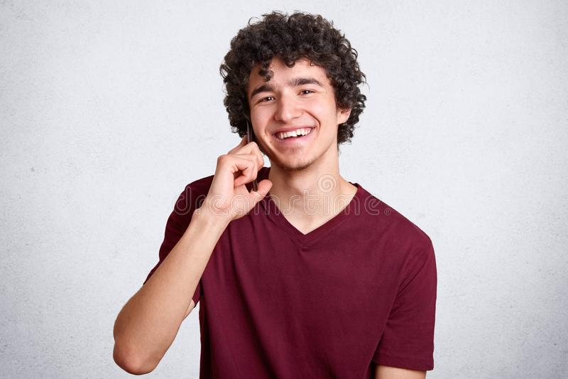 Studio shot of curly cheerful European male with little beard, curly hair, wearing casual dark red t shirt, isolated over white royalty free stock photography