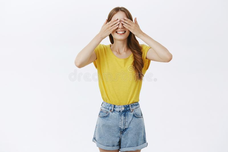 Studio shot of cute charismatic woman standing with anticipation over gray background closing eyes and holding palms on. Sight while waiting for surprise royalty free stock image