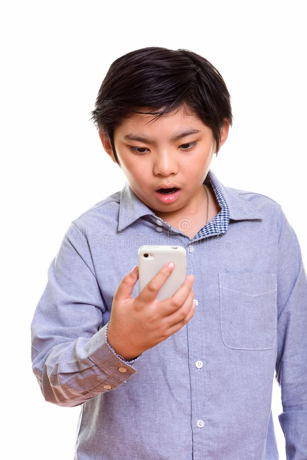 Studio shot of Japanese boy isolated against white background. Studio shot of cute Japanese boy using mobile phone and looking shocked stock images
