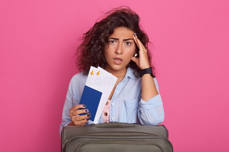 Studio shot of dark haired woman isolated over pink background, looks tired and astonished, posing with suitcase and passport and. Tickets in hand, keeps hand royalty free stock image