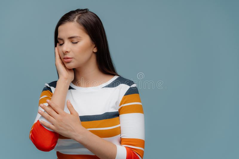 Studio shot of dark haired woman touches cheek, suffers from toothache, has painful feelings, has eyes closed, wears casual jumper royalty free stock image