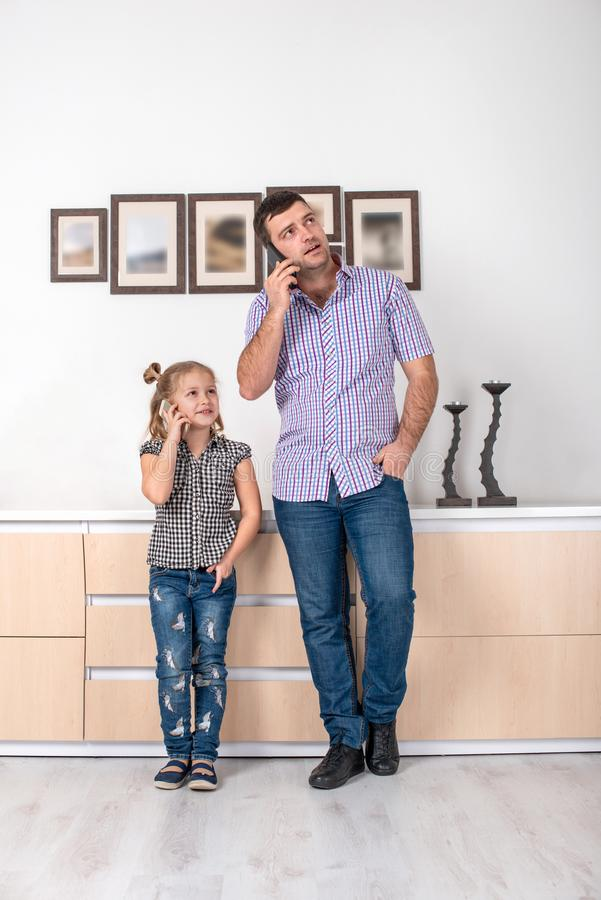 Studio shot of a little girl and her dad standing at home and talking on the phone the same way. Daughter imitates her father royalty free stock images