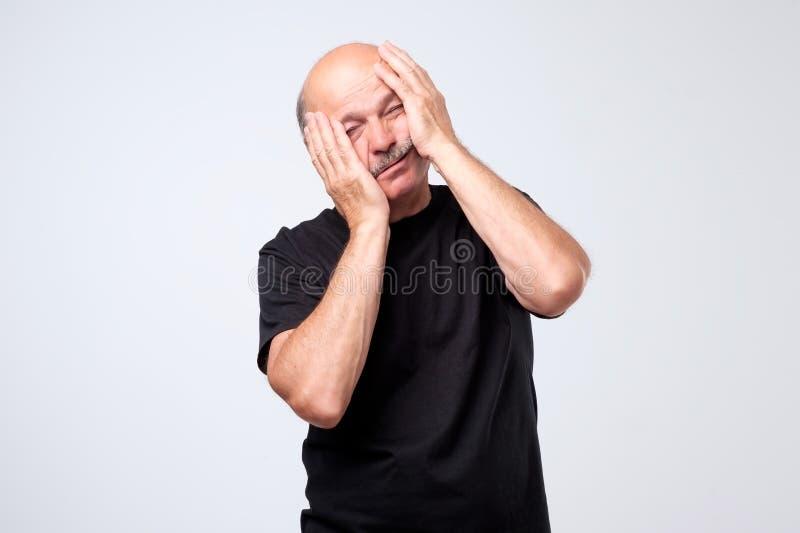 Studio shot of desperate upset senior man holding hands on face royalty free stock photography