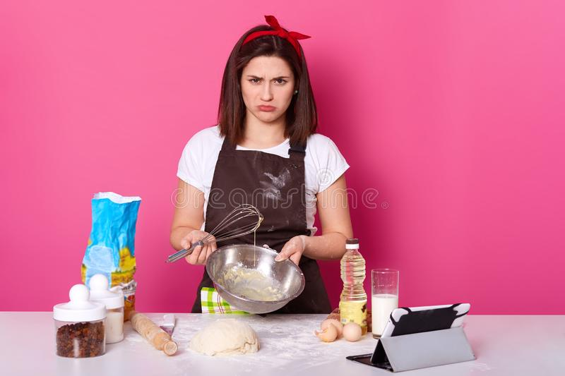 Studio shot of disappointed brunette housewife standing at kitchen with unpleasant facial expression, holding bowl and whisk in royalty free stock photography