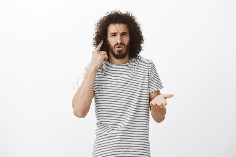 Studio shot of displeased confused bearded male student in striped t-shirt, pointing at ear and frowning, cannot hear stock photography