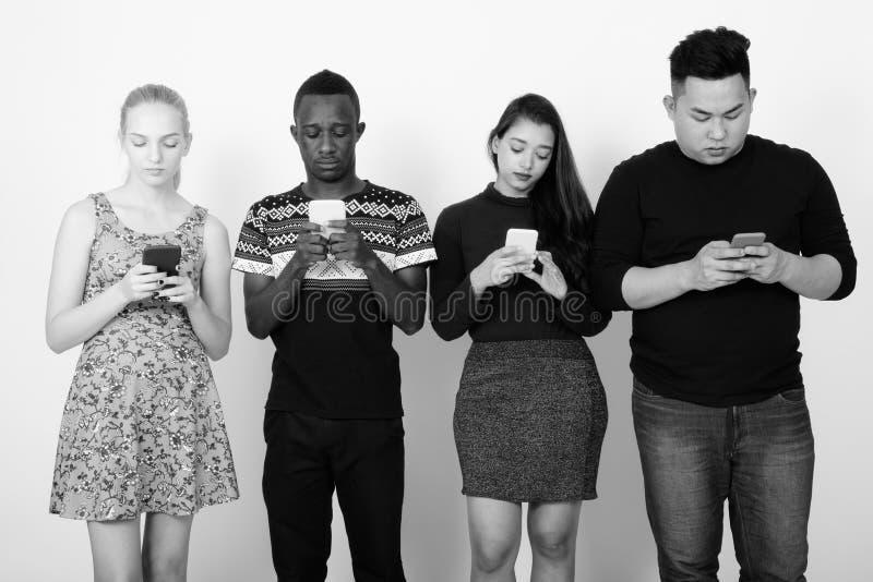 Studio shot of diverse group of multi ethnic friends using mobile phones together. Studio shot of multi ethnic group of friends together as diversity concept stock image