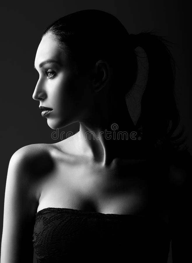 Studio shot: dramatic portrait of beautiful young woman. Profile view. Black and white royalty free stock photography