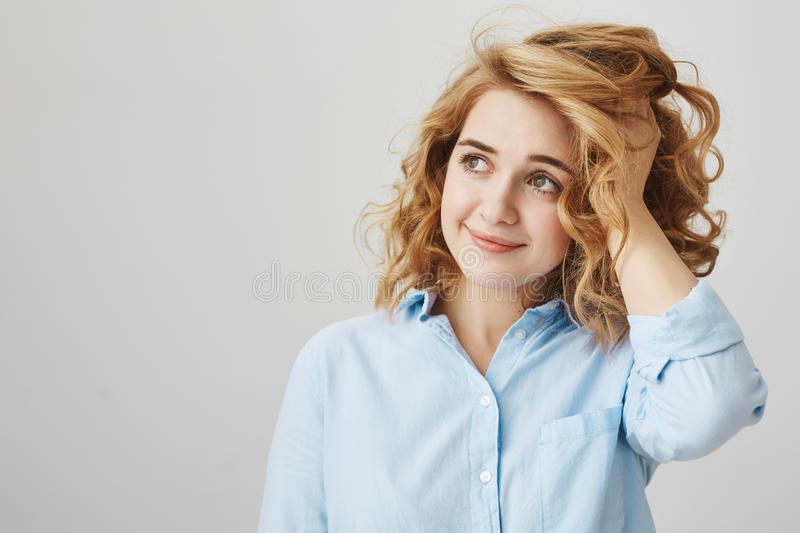 Studio shot of dreamy attractive woman with short curly hair looking aside with tender smile, touching haircut and royalty free stock photos