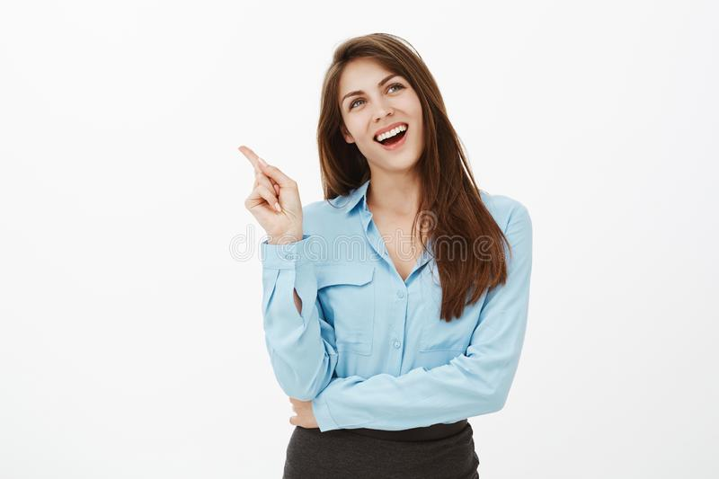 Studio shot of dreamy charming female office worker in blue blouse, holding hand crossed and raising index finger. Smiling broadly while gazing up with pleased stock photos