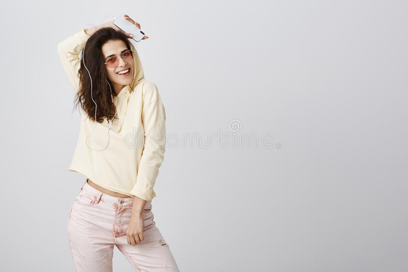 Studio shot of expressive playful young woman with curly hair posing in yellow cropped hoodie and trendy sunglasses stock image