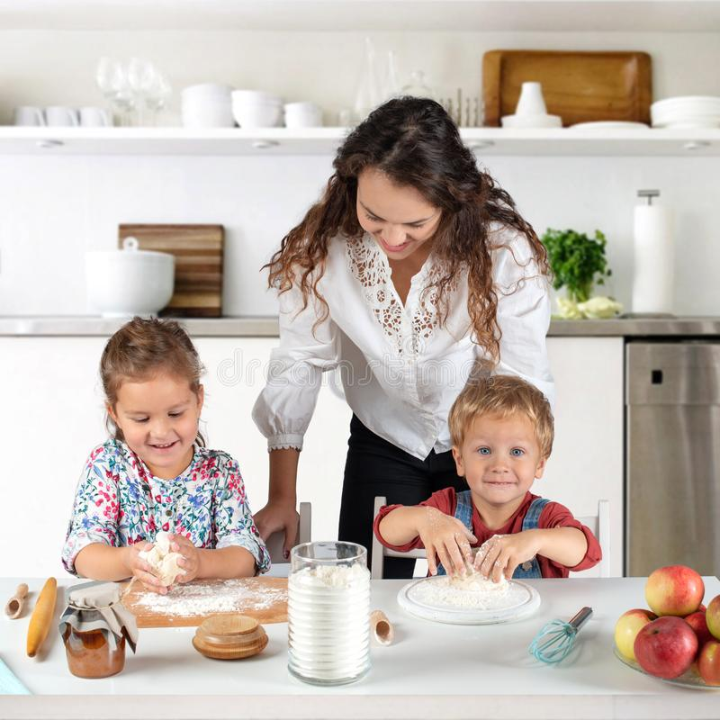 Studio shot of a family in the kitchen at home. Small children, a girl and a boy, learn to make dough rolls with their mother or stock photography