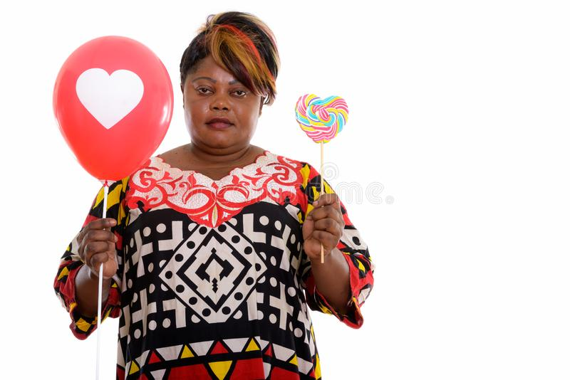 Studio shot of fat black African woman holding heart shaped loll stock image
