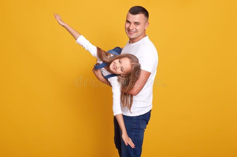 Studio shot of father plays with cute little girl, child dressed in casual clothes, handsome man holding her little daughter like stock photography