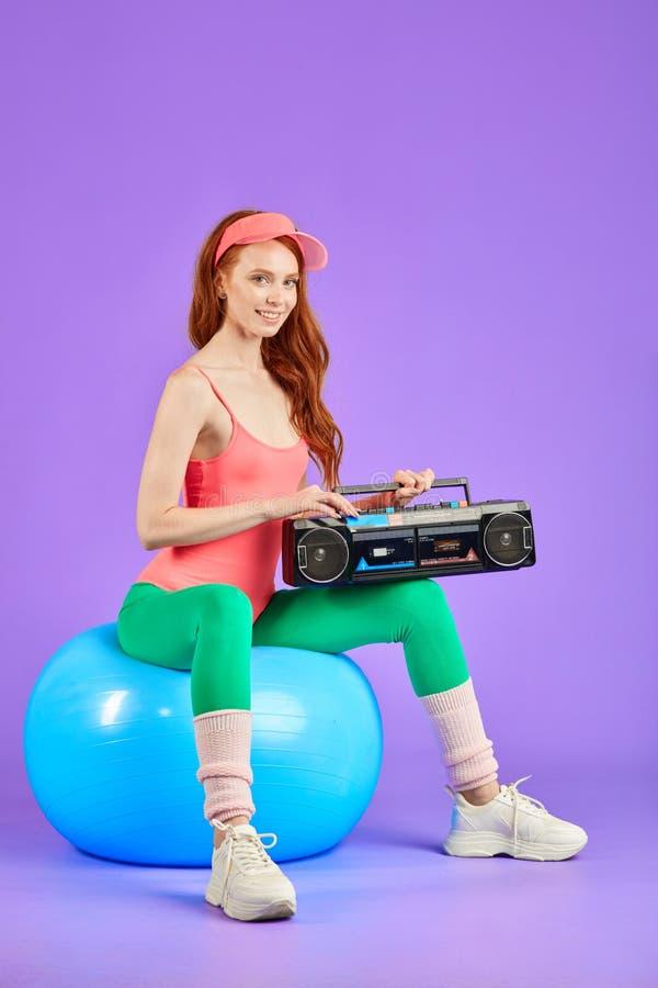 Studio shot of female model poising at camera for retro style photoshoot with portable cassette player. Female posing for retro style photoshoot, sitting on blue stock photo