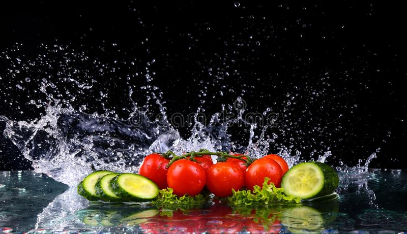 Studio shot with freeze motion of cherry tomatoes and slices of cucumber in water splash on black background royalty free stock images