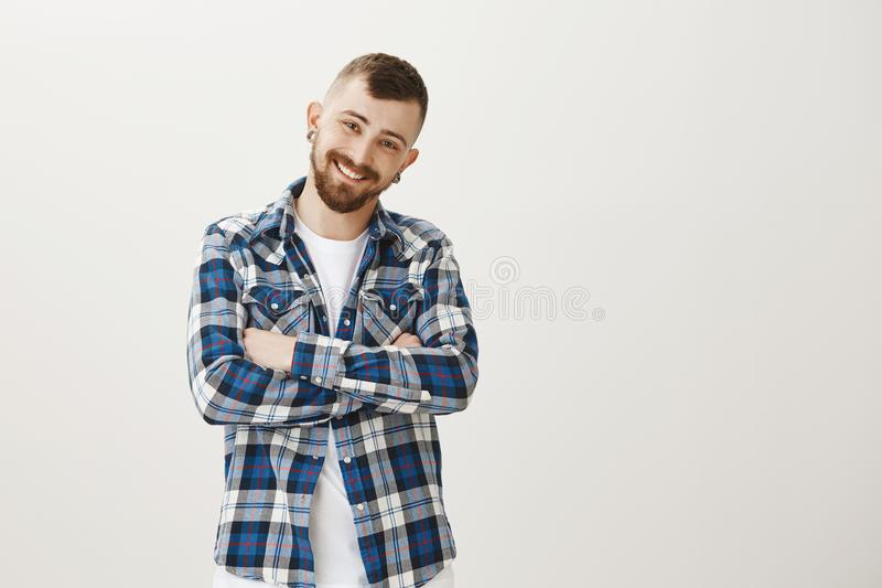 Studio shot of friendly handsome young boyfriend with beard, standing with crossed hands and smiling joyfully, blushing stock photos