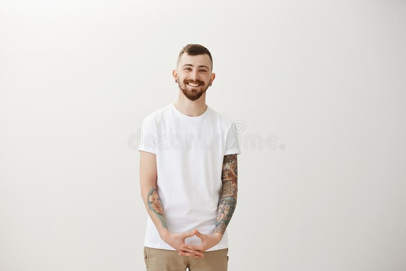 Studio shot of friendly happy young guy with beard and cool tattoos, holding hand in triangle over pants and smiling stock photography