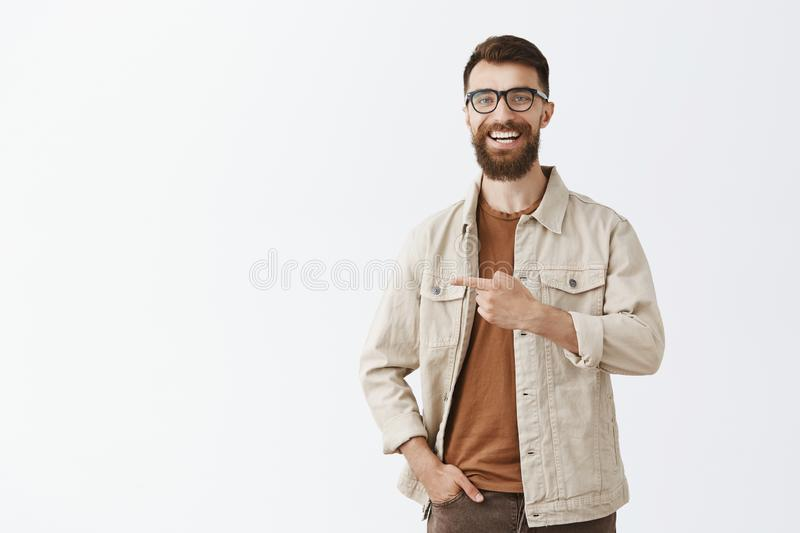 Studio shot of friendly joyful handsome guy with long beard and stylish moustache in trendy glasses and outdoor beige. Jacket laughing out loud having funny and royalty free stock photos