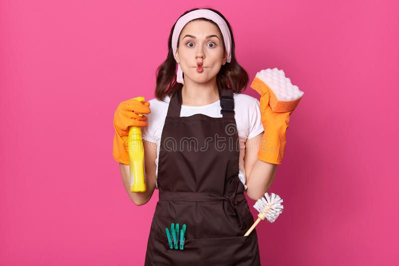 Studio shot of funny charming young Caucasian housewife wearing headband, orange rubber gloves and brown apron, attractive lady royalty free stock photo
