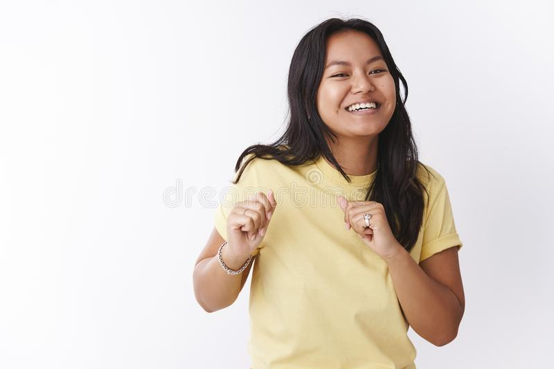 Studio shot of funny and enthusiastic upbeat joyful female in yellow t-shirt making dance moves shaking body and hands. Attending awesome party with cool music royalty free stock images