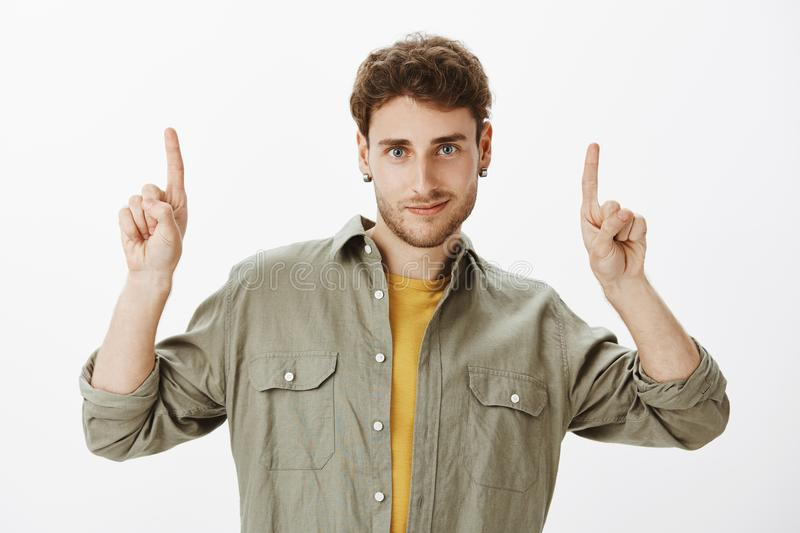Studio shot of good-looking curly-haired guy with beard, posing over gray background with lifted index fingers, pointing royalty free stock images