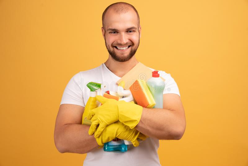 Studio shot of good looking pleased man with bald head, hugs cleaning detergents, wears t shirt, isolated over yellow background.  stock photos