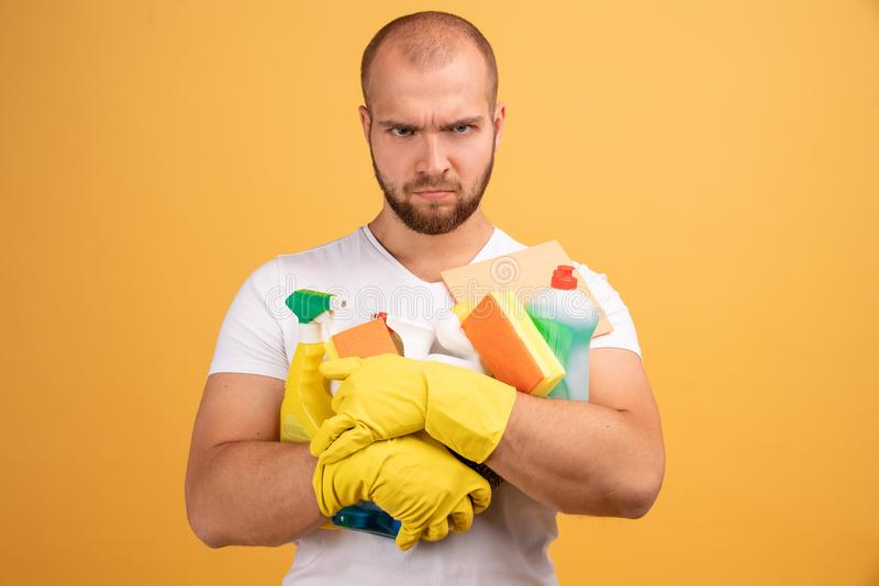 Studio shot of good looking unhappy man with bald head, hugs cleaning detergents, wears t shirt, isolated over yellow background.  royalty free stock images