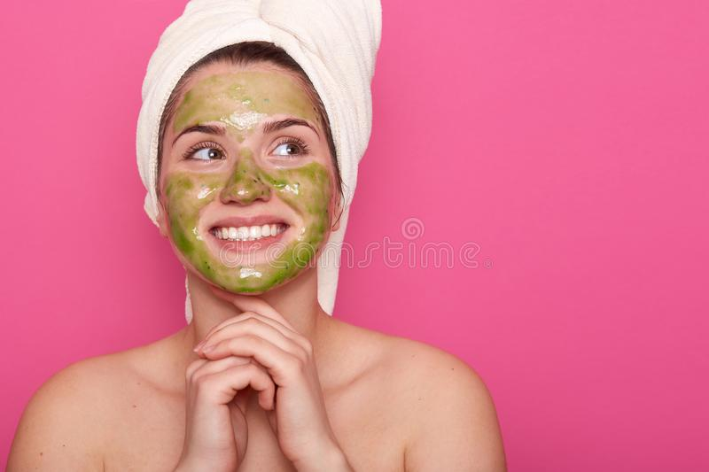 Studio shot of good looking woman with dreamy facial expression, has daily spa procedures, healthy fresh skin, looks aside, keeps royalty free stock photo