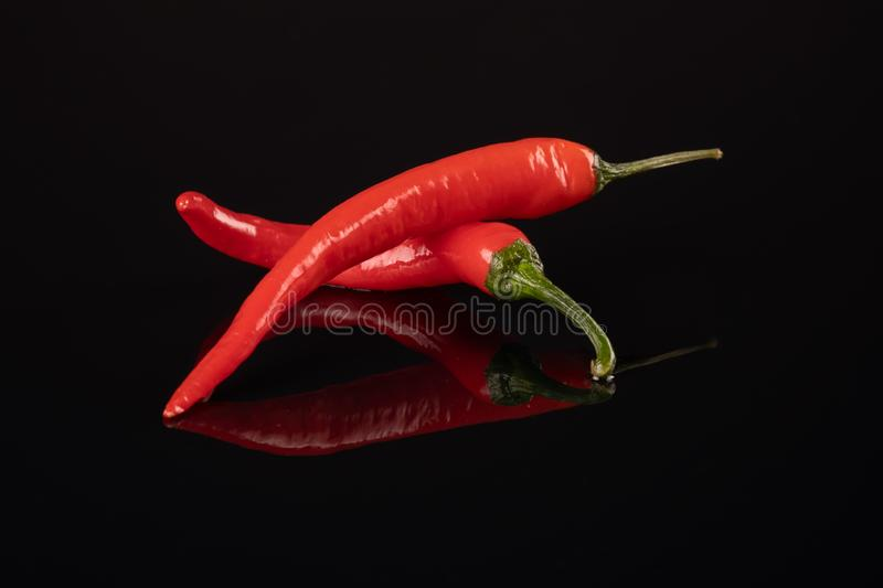 Studio shot of group of red chilli peppers on a black background royalty free stock photography