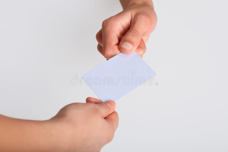 Studio shot of hand giving blank plastic card or paper flyer,  on white background, copy space for your advertismant or. Promotion text, paymant and shopping stock photo