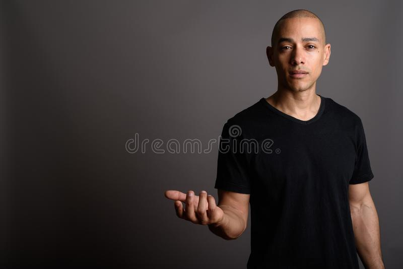 Handsome bald man with arm raised shrugging shoulders. Studio shot of handsome bald man wearing black shirt against gray background royalty free stock images