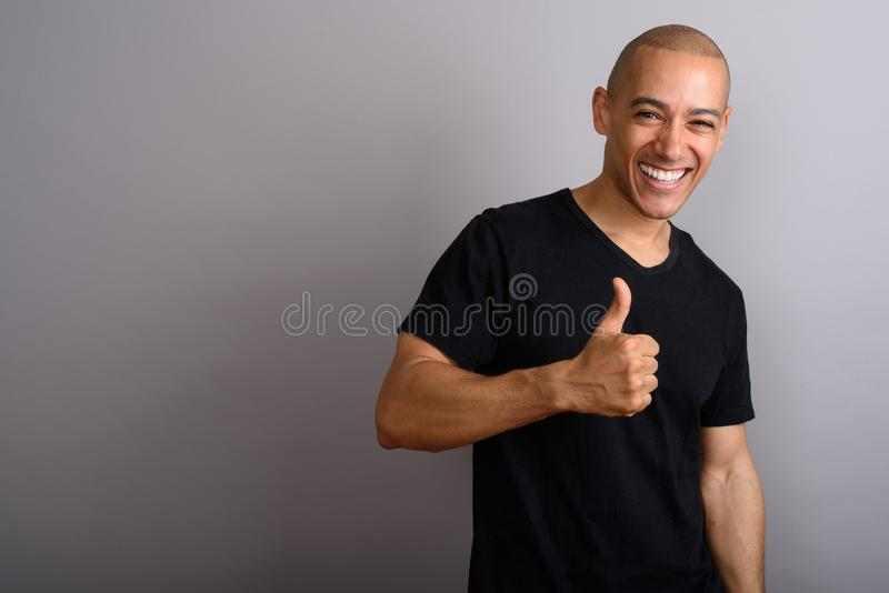 Handsome happy bald man smiling and giving thumb up stock image