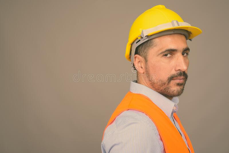 Handsome bearded Persian man construction worker against gray background royalty free stock photo