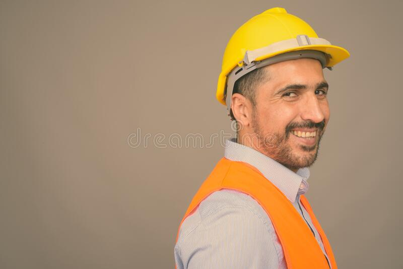 Handsome bearded Persian man construction worker against gray background royalty free stock image