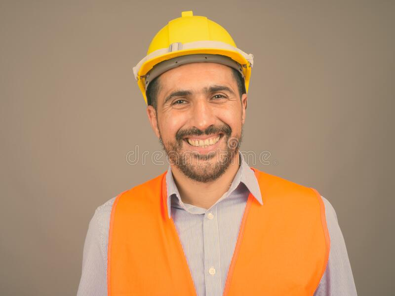 Handsome bearded Persian man construction worker against gray background stock photos