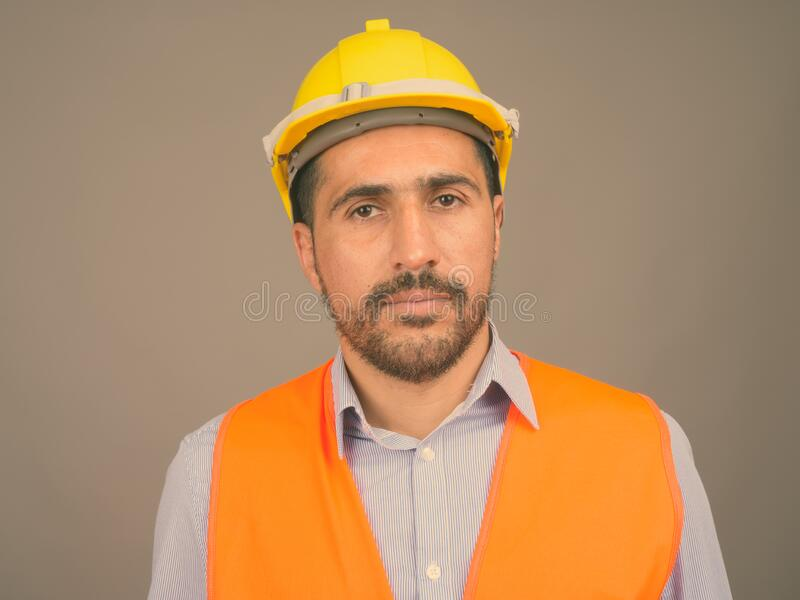 Handsome bearded Persian man construction worker against gray background stock images