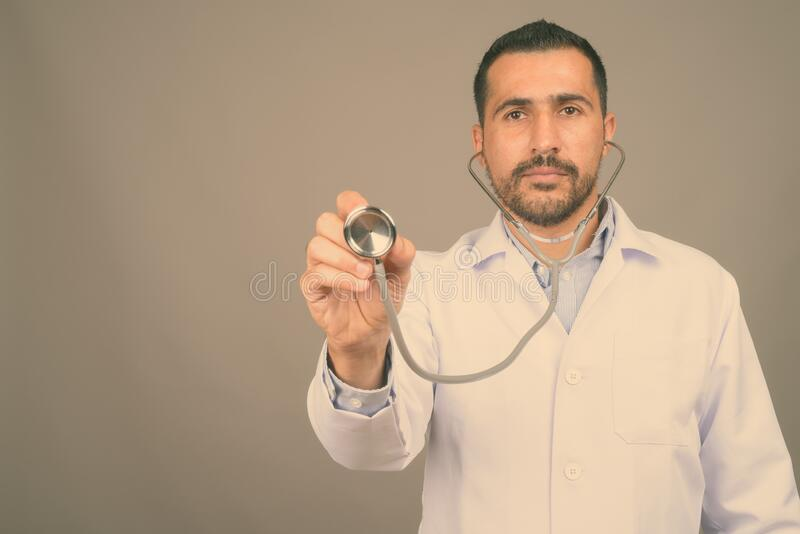 Handsome bearded Persian man doctor against gray background. Studio shot of handsome bearded Persian man doctor against gray background royalty free stock images