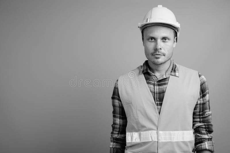 Handsome man construction worker against gray background. Studio shot of handsome man construction worker against gray background in black and white royalty free stock photo